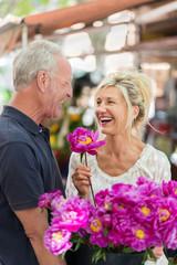 glückliches älteres ehepaar kauft blumen
