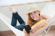 frau liegt in der hängematte und tippt auf smartphone