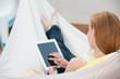 frau in der hängematte tippt auf tablet-pc