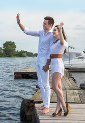 Guy holds the girl's hand on a wooden pier near the water.