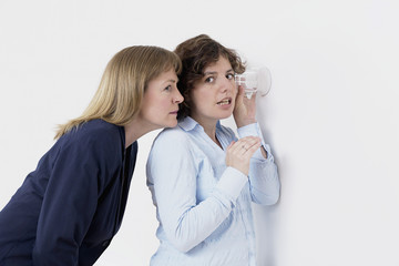 woman listening to conversation through wall