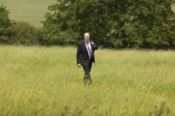 white business man walking in an english meadow