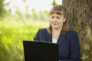 businesswoman working on computer in field under tree