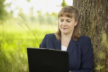 businesswoman working on computer in field under tree