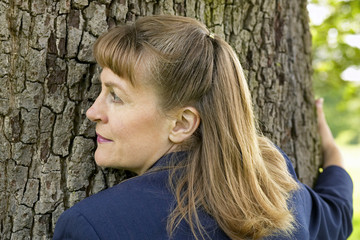 business woman hugging a tree and listening