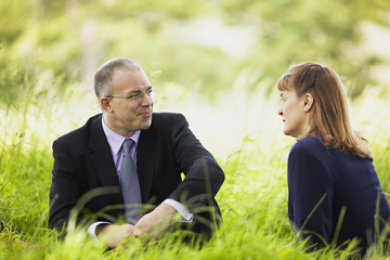 business man and woman meeting in field under shade of a tree