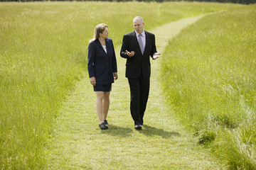 business man and woman walking across field talking