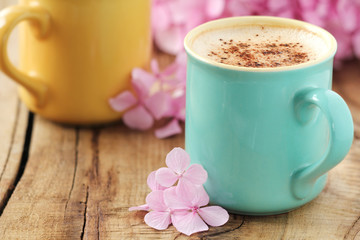 Two cups of cappuccino and pink hydrangea on shabby wooden table