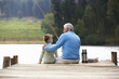 Senior man fishing with grandson - 66744934