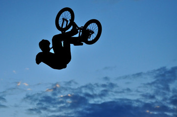 Silhouette of a BMX rider making a bike jump in the air