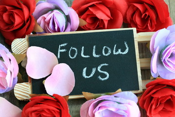 "message of ""Follow Us"" with flowers in the background"