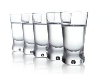 Five glasses of vodka isolated on white