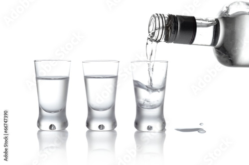 Poster Alcohol Bottle and glasses of vodka poured into a glass isolated on whit