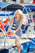 Adorable blonde sitting against a backdrop of yachts and the sea