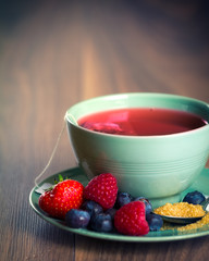 Cup of fruit tea with berries on wooden table with copy space