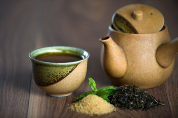 Cup of black  tea with mint leaves and brown sugar