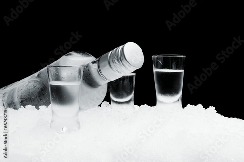 Bottle with glasses of vodka lying on ice on black background