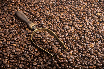 roasted coffee beans with retro bronze scoop