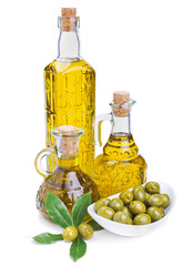 bottles of olive oil and green olives with leaves