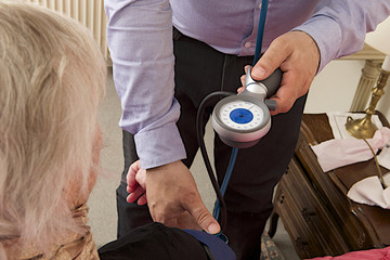 Male doctor taking the pulse of an older woman