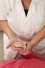 Hand of woman touching cheerfullly senior woman at clinic