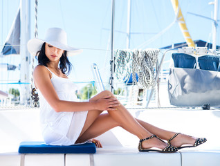 Young and lovely brunette woman relaxing on a boat
