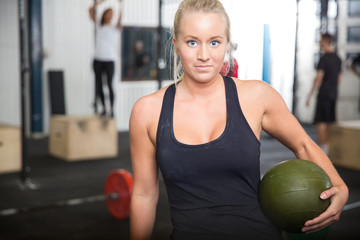 Fitness woman with slam ball at gym center