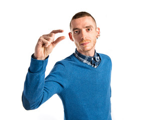 Young man doing a tiny sign over white background
