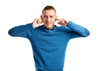 Redhead man covering his ears over white background
