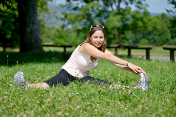 sporty young woman makes stretching exercises on grass