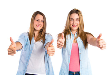Friends with thumbs up over white background