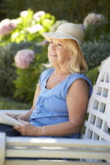 Senior woman reading in garden