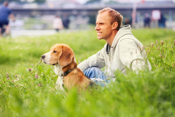Man with his dog sitting in green grass