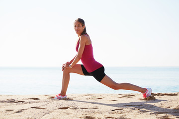Attractive sports girl doing stretching exercise on the beach