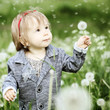 Smiling baby girl with dandelion on green grass