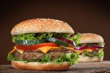Two delicious hamburgers on wood background.