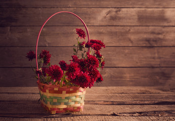 flowers in basket on wooden background