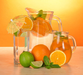 Jugs with drinks, glass, juicy lime and oranges