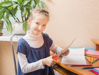 Girl with scissors cuts paper at home
