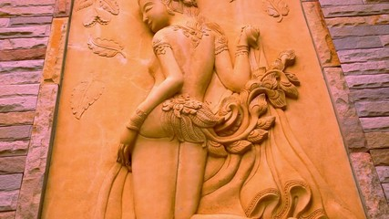 Thai ancient stone carving in woman view on wall. Macro