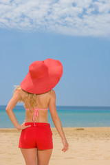 woman on tropical beach in red shorts