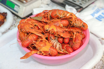 Plate with red boiled crawfish on a table close up
