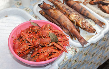 Plate with red boiled crawfish and smoked fish on a table close