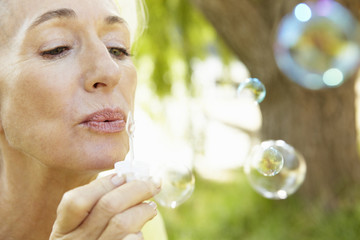 Senior woman blowing bubbles outdoors
