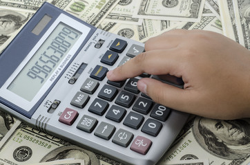 Finger pressing on a calculator of US dollars as a background