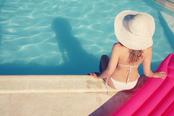 Young woman sitting at the swimming pool