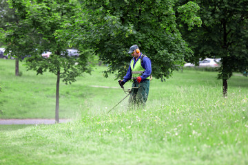 Worker cutting grass in the park