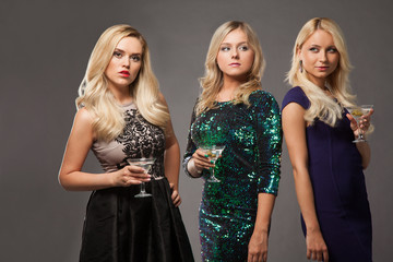 three blonde girls wearing evening dresses driknking martini