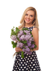 blonde smiling girl in dot dress holding flower; bouquet of lila