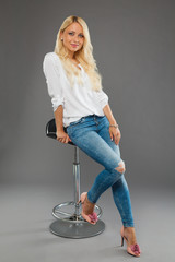 blonde girl sitting on the chair wearing jeans and white shirt